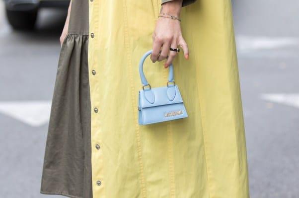 Woman holds mini designer bag from Jacquemus