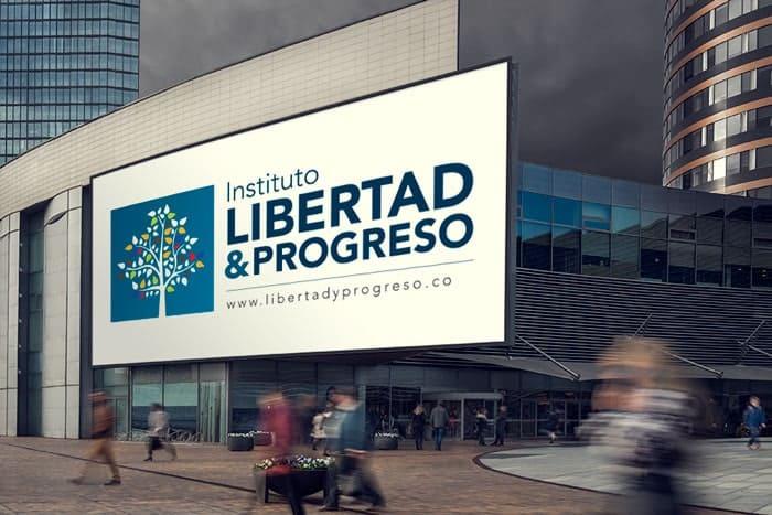 Fachada de un edificio con gente caminando al frente. En la fachada del edificio está la marca Libertad y Progreso Exhibida.
