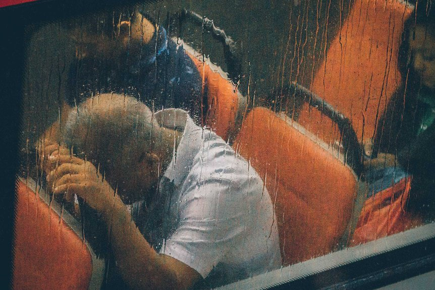 A rainy bus window and inside a man leaning his head on the seat in front of him.