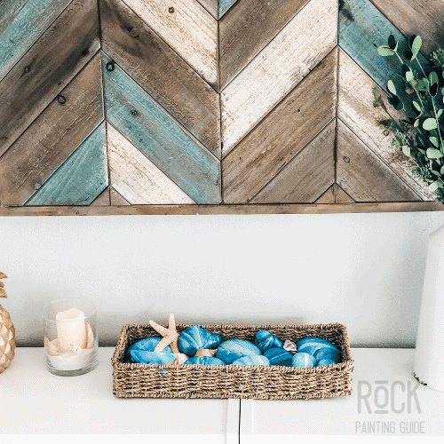 beach painted rocks in a jute basket displayed on a bookcase