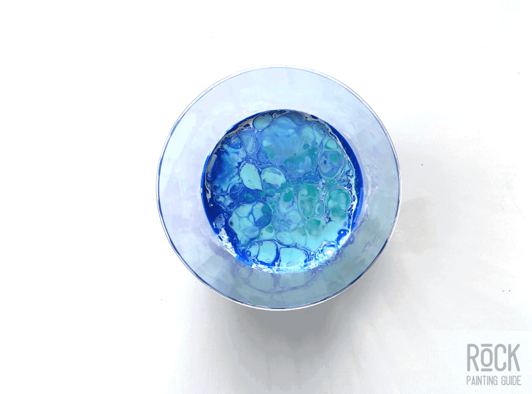 a cup of a dirty pour with blue, white, and green paint