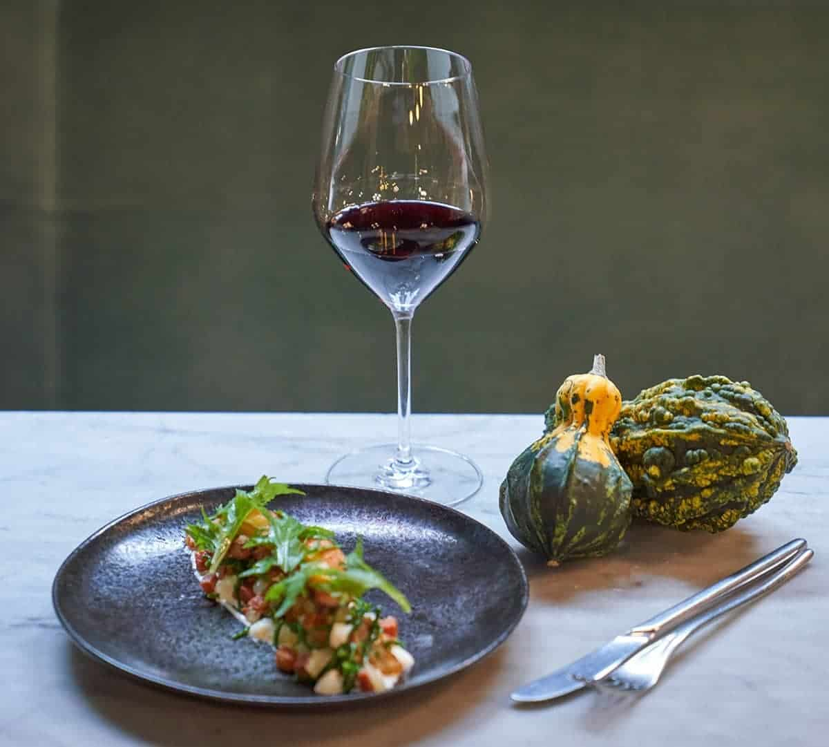 A glass of red wine shown with a plate of food and a couple gourds.