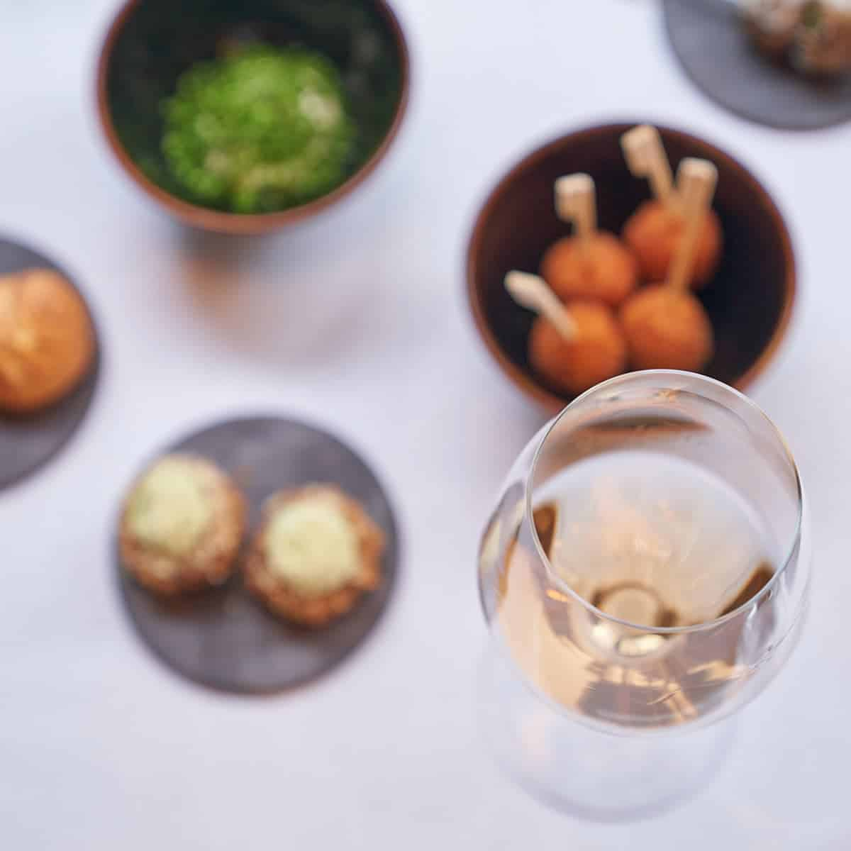 A glass of wine with several snacks and finger foods.