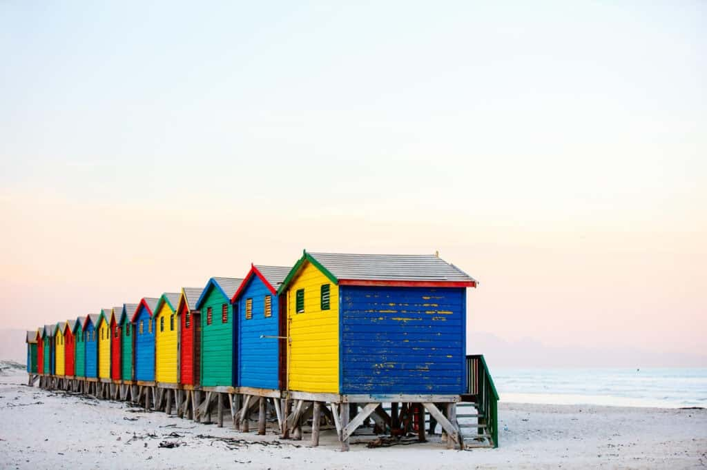 A row of wooden huts painted in rainbow colors on the beach