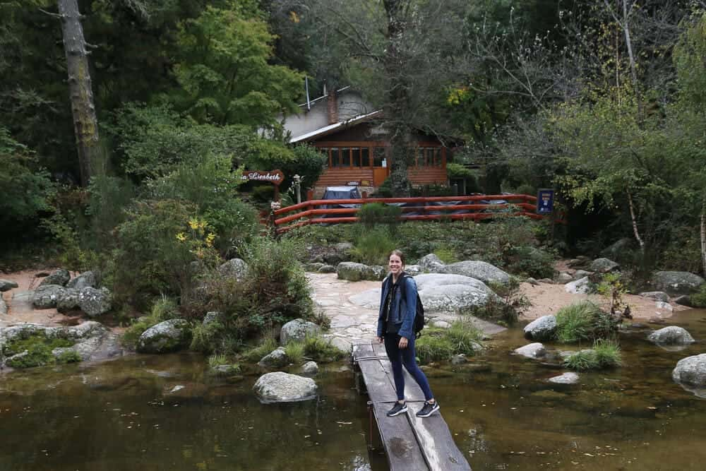 A woman stands on a wood plank bridge over a creek in a pine forest in front of a wooden cabin