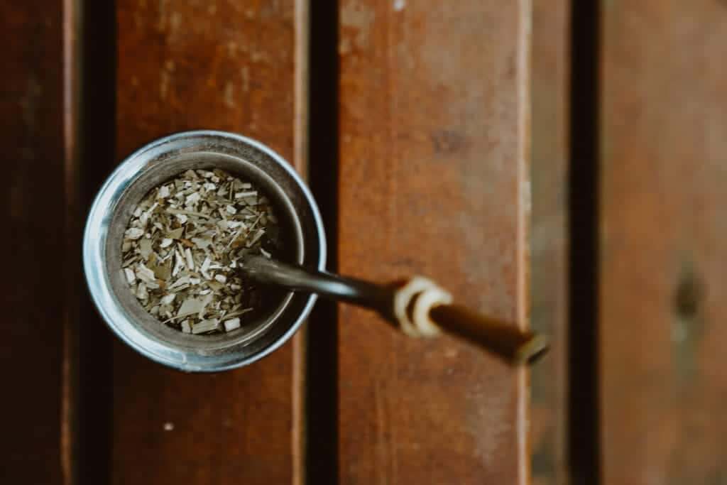 A cup of Yerba Mate and a bombilla straw on a wooden deck