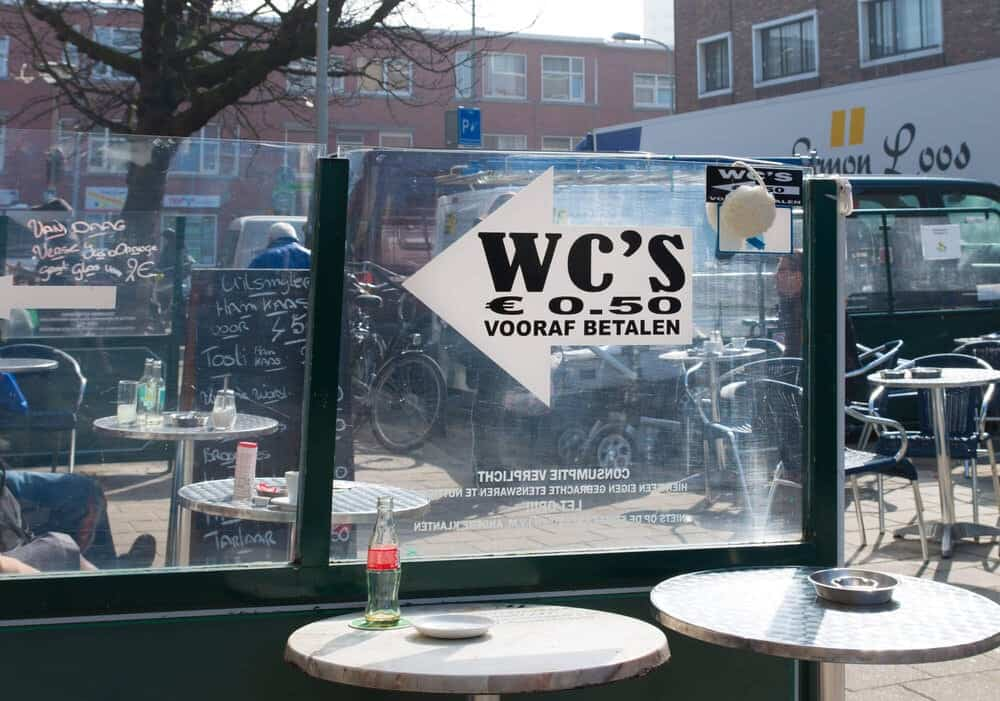 Two round tables at a sidewalk cafe by a glass divider with a WC sign
