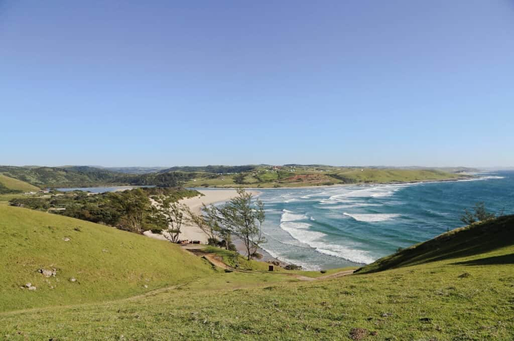 Ocean waves wash up to the beach at the foot of large hills