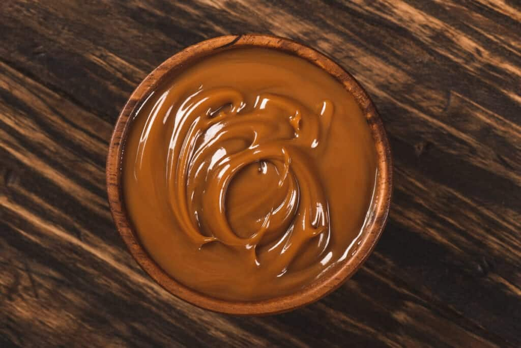 A bowl of creamy dulce de leche on a wooden table