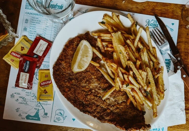 A breaded schnitzel and french fries on a plate with ketchup packets