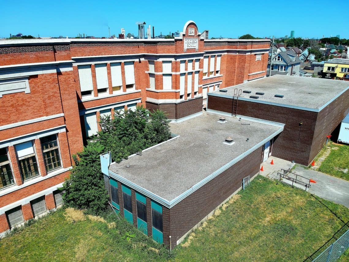 Low aerial view of the Gibson School building seen from the Barton Street (south) side, overlooking the midcentury addition