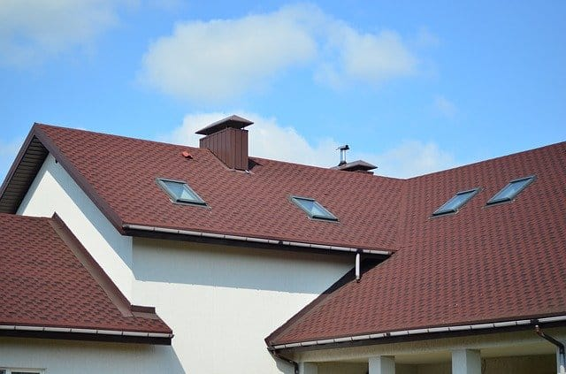 asphalt shingle roof with skylights, flashing, gutters, and solar panels