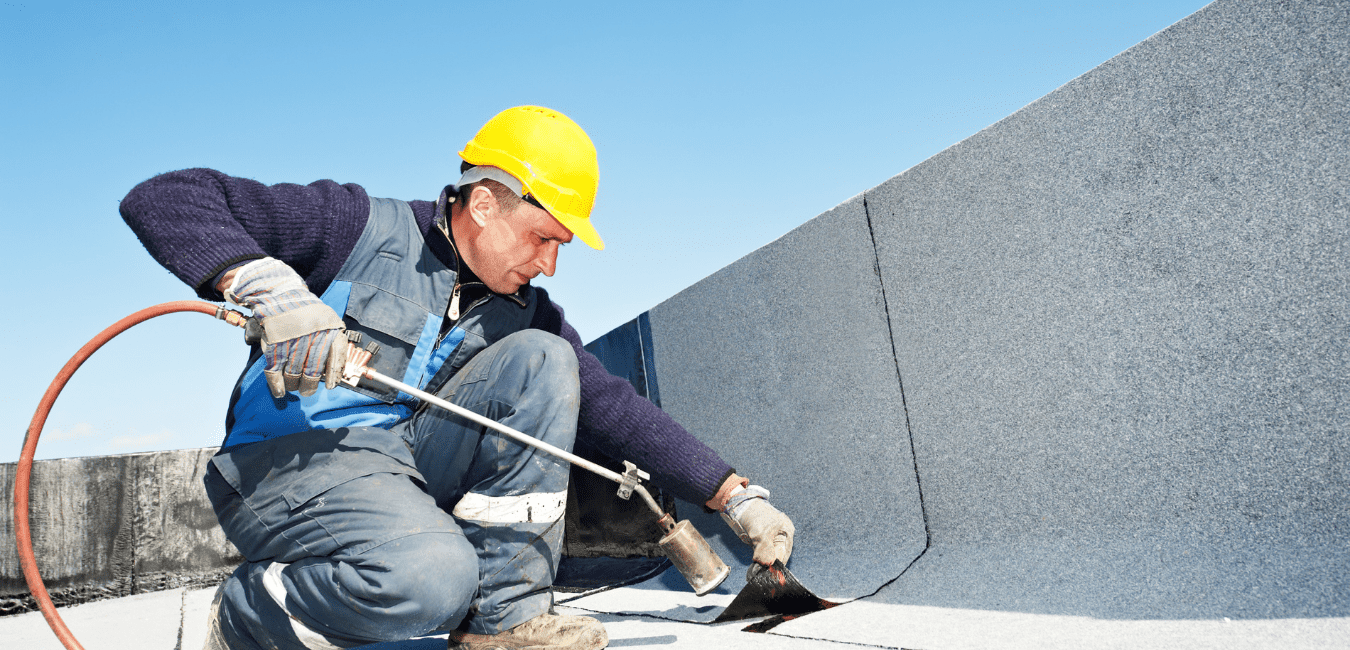 man using heat to seal seams on roof