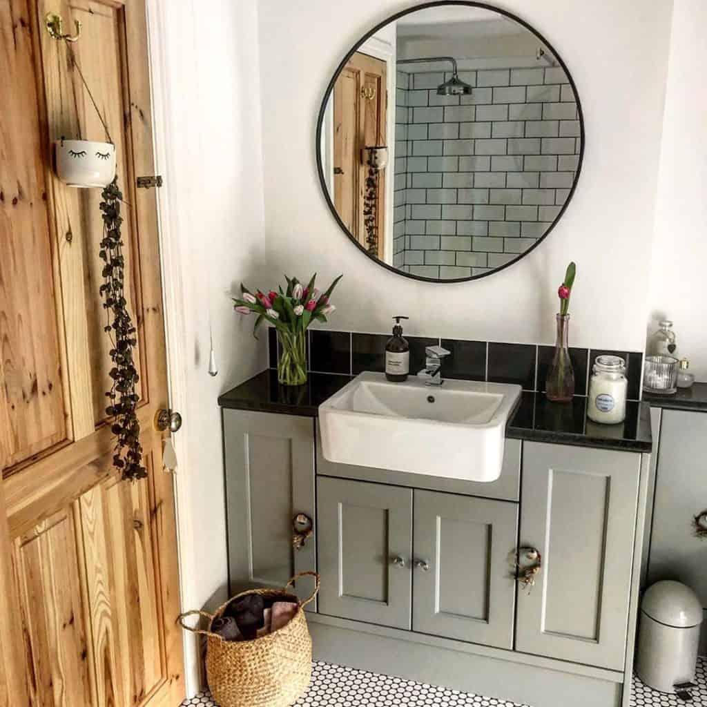 bathroom cabinet idea in bathroom with gray vanity and farmhouse apron sink in bathroom