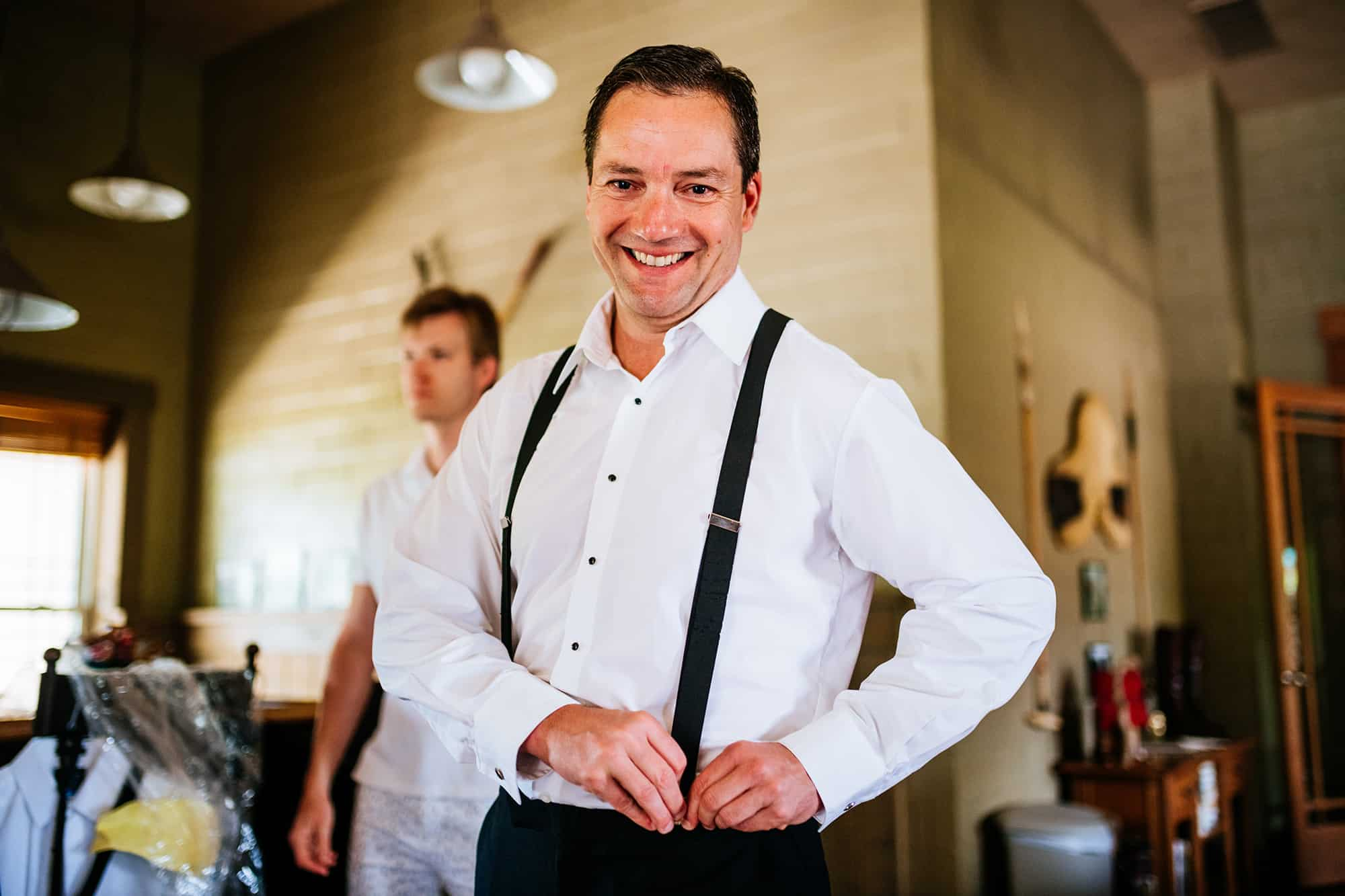groom putting on suspenders