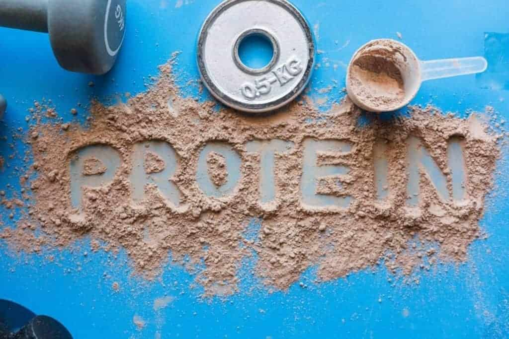 A pile of  whey protein concentrate spread across a blue table with the word protein written in the middle.