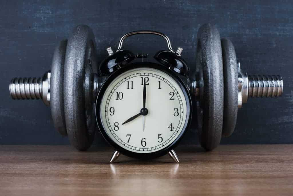 picture of a clock in front of dumbbells asking when is the best time to take creatine
