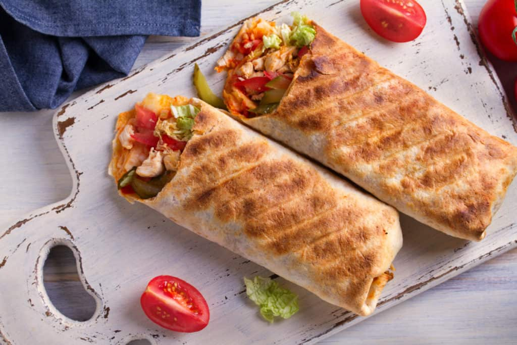 breakfast burritos with tomatoes, pickles, cabbage and onion on a white chopping board and wooden table. Tortilla, the perfect on the go bodybuilding breakfast
