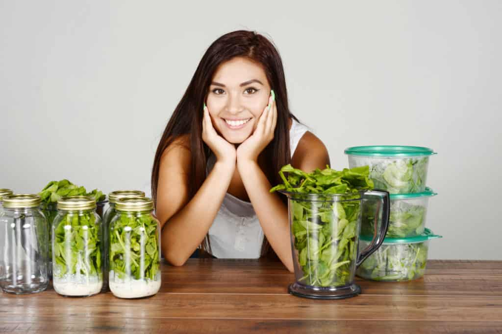 Picture of a young brunette leaning on a table with tupperware containers on either side of her because she is  doing meal prep for the week