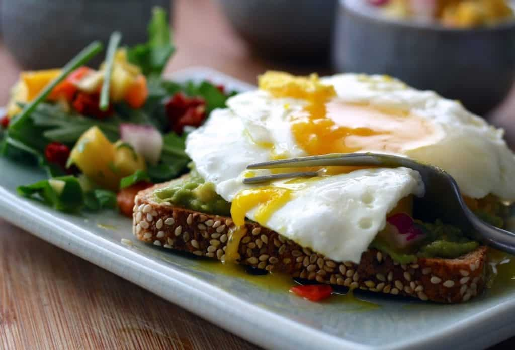 A picture of avocado toast with eggs sunny side up and a salad of greens, the perfect bodybuilding breakfast.