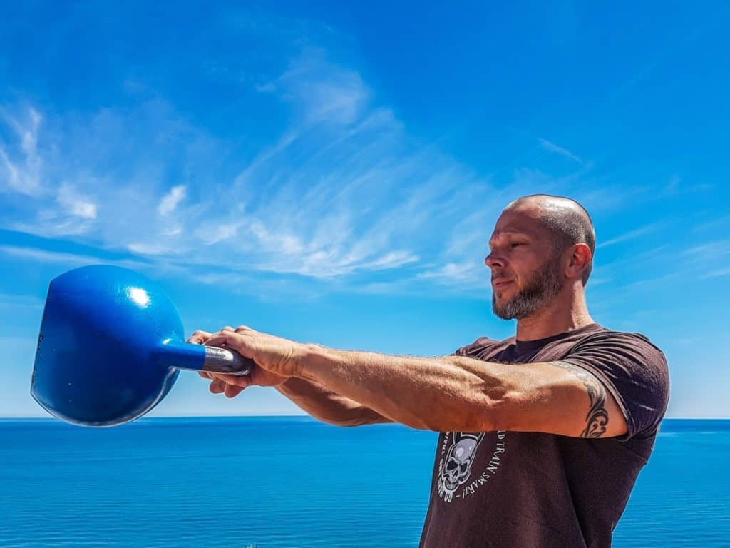 a fit male swinging a kettlebell as part of a exercise to lose weight