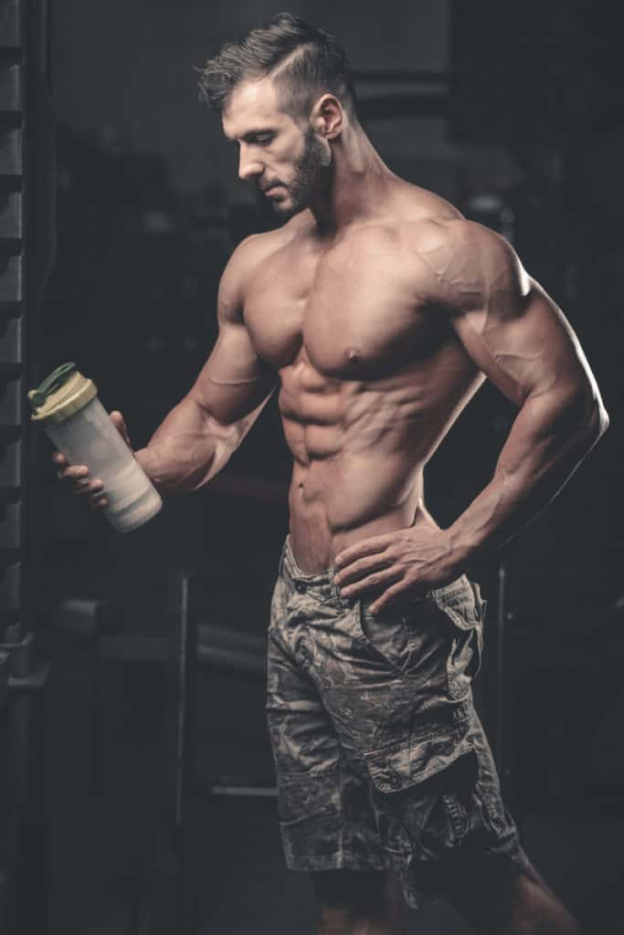Muscular caucasian man on diet resting after exercise And drinking creatine monohydrate powder from shaker in the gym