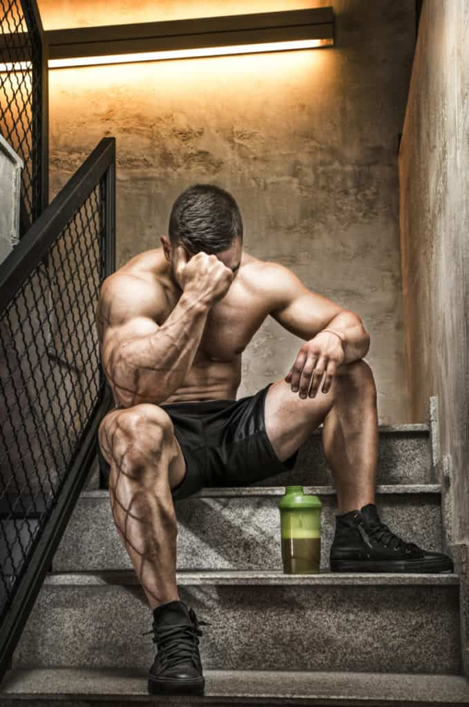 a very fit male sitting on steps after a very hard workout drinking creatine.
