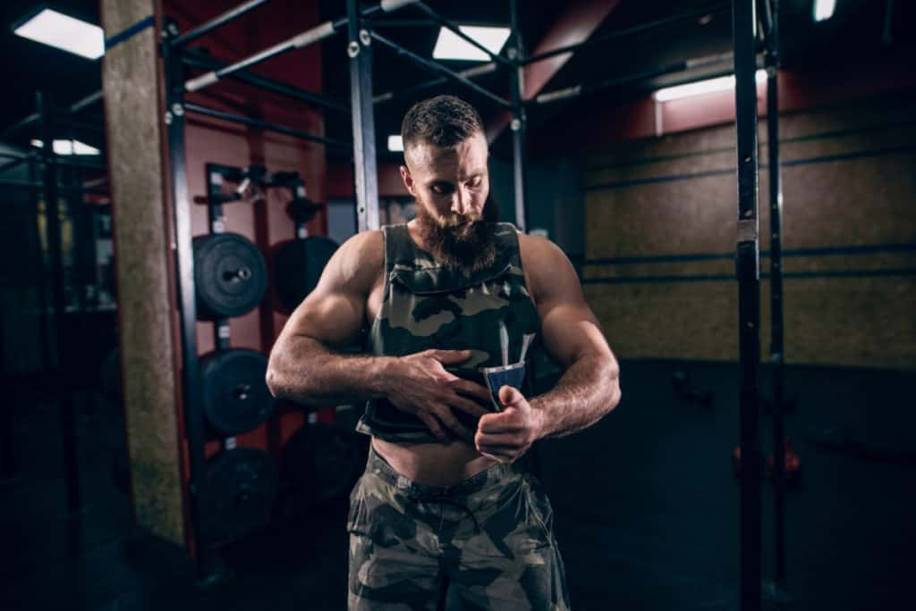 Muscular caucasian bearded man tightening up military style weighted vest in crossfit gym. Weight plates and kettlebells in background.