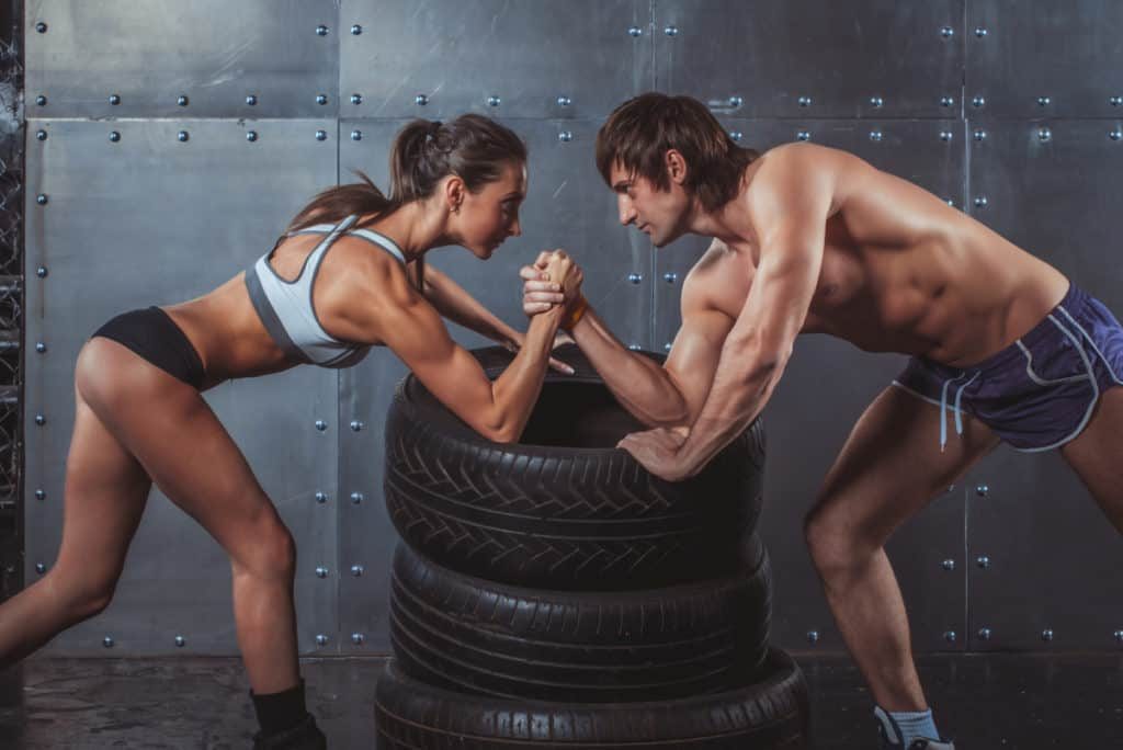 Athlete muscular sportsmen man and woman with hands clasped arm wrestling challenge between a young couple Crossfit fitness sport training lifestyle bodybuilding concept