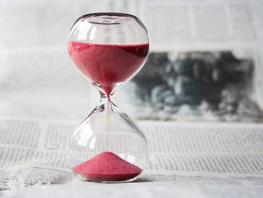 A picture of an hourglass with red sand depicting the best time to take creatine to avoid creatine bloating