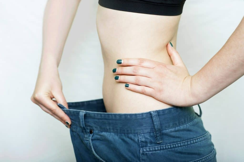 A woman with a tiny waist wearing pants that are too big for her.
