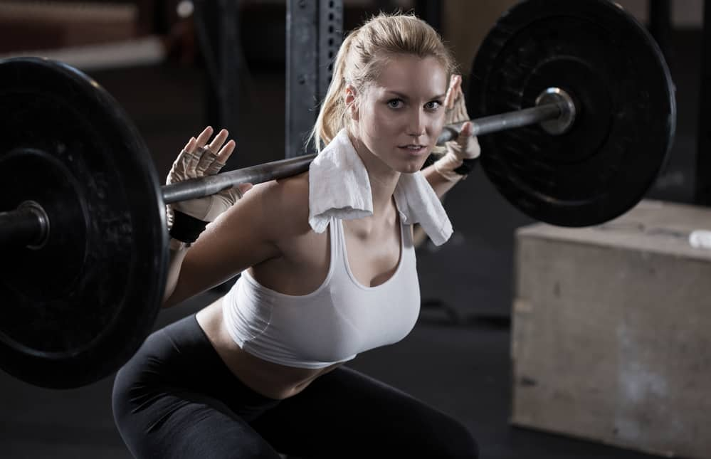 An image of a young woman performing below parallel squats.