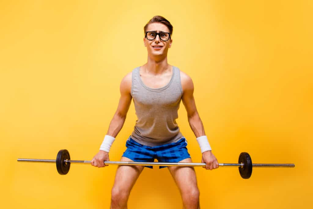It seems I'm not in shape! Portrait of masculinity man with a confused and puzzled face can not lift a heavy barbell isolated on bright yellow background taking D-bal to gain muscle
