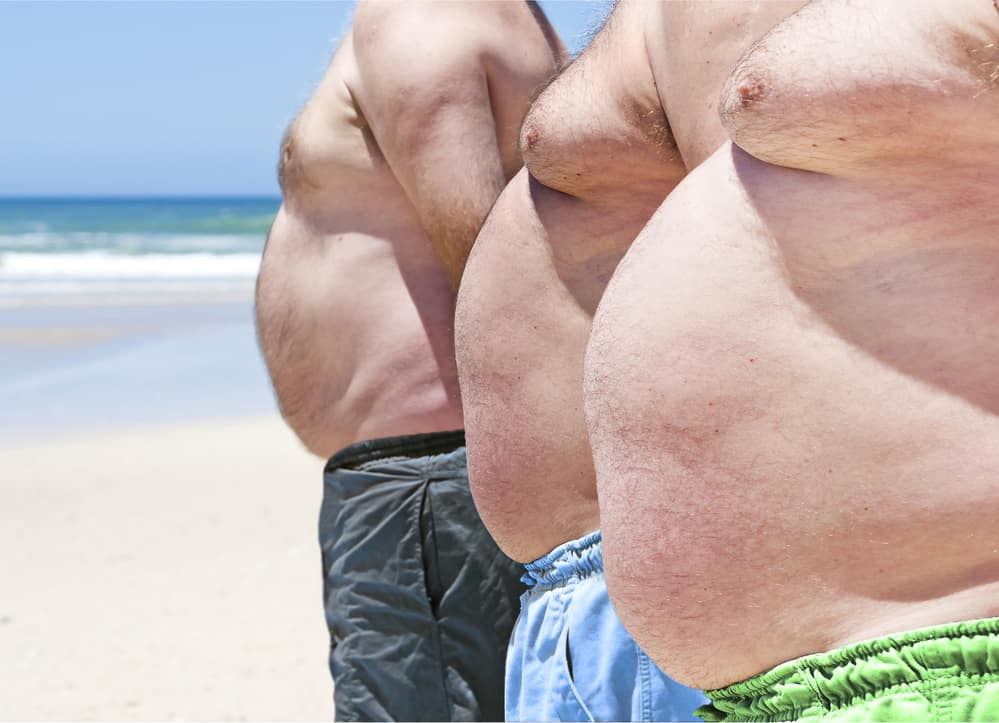 Three men on the beach with there shirts using gynectrol to reduce the size of their breast tissue