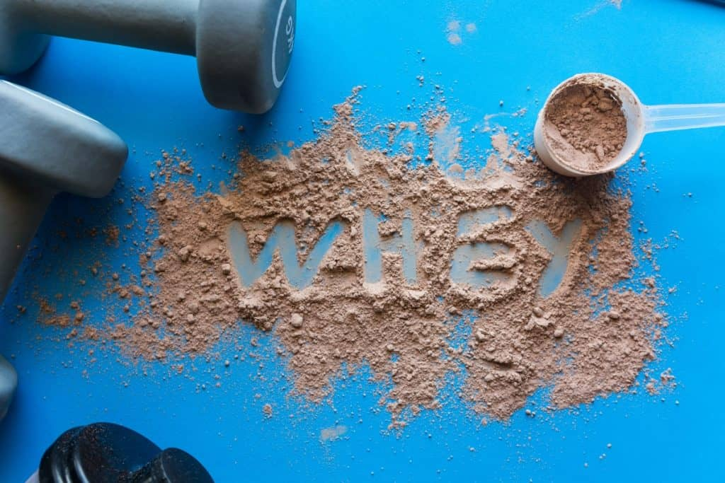 a picture of spilled whey protein powder with the word whey written in the middle of it next to dumbbells on a blue background. Whey is a natural thermogenic food