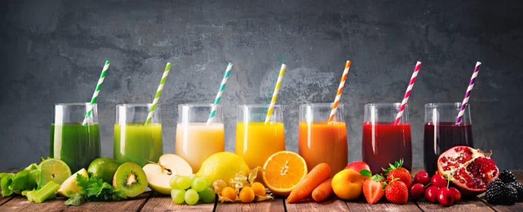 7 different fruit juices with the fruit they're made of sitting in front of them on a wooden table