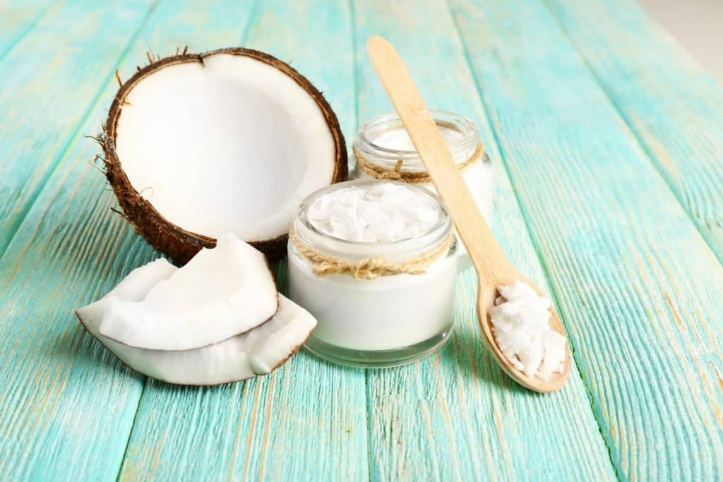 a coconut cut in half laying on 2 jars with coconut oil in them with a wooden spoon leaning on the jars