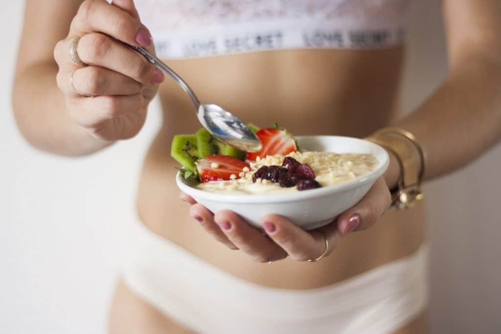 A young fit woman with a tight flat stomach holding a bowl of cottage cheese showing how a natural thermogenic food like cottage cheese can burn away belly fat