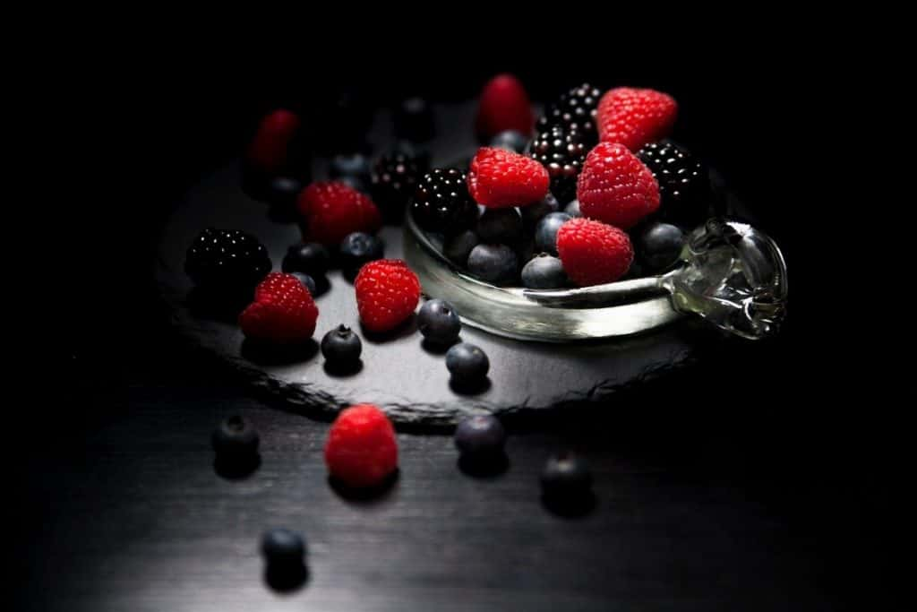 a bowl sitting on a black table with a black background holding a mix of berries including strawberries, blueberries, and blackberries high in antioxidants to help you lose weight