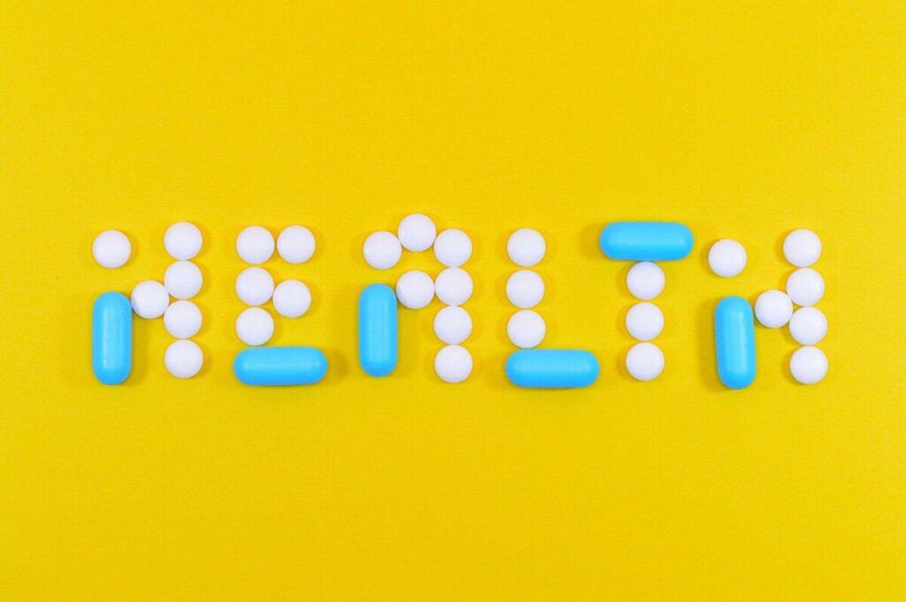 a yellow background with the word health written out of blue and white pills
