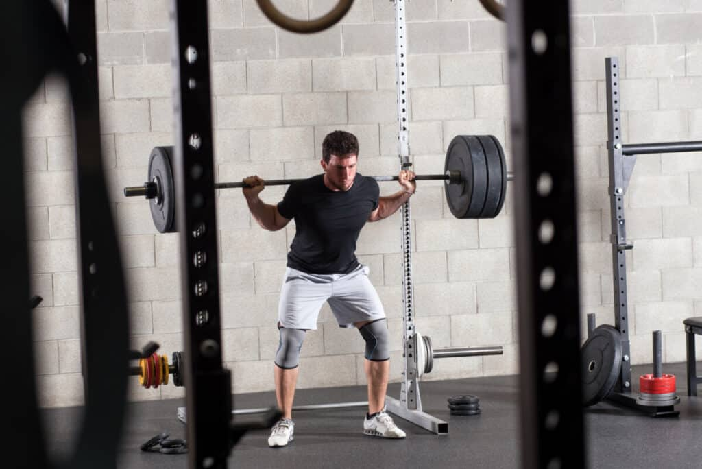 Bodybuilder exercising on squat rack in gym, weight equipment in foreground