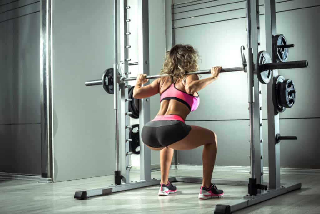 Attractive young woman doing squats at Smith rack machine in modern fitness center. Toned image.
