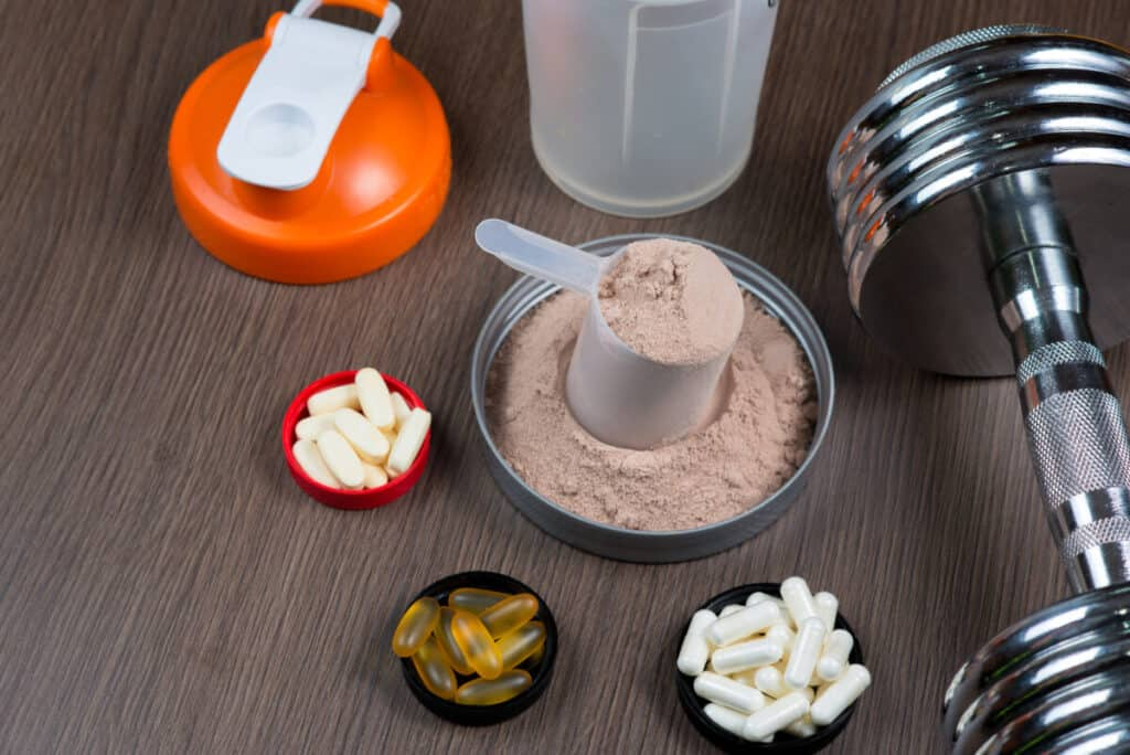 creatine powder, capsules, and liquid in a measuring bucket with a metal dumbbell and shaker on a wooden background