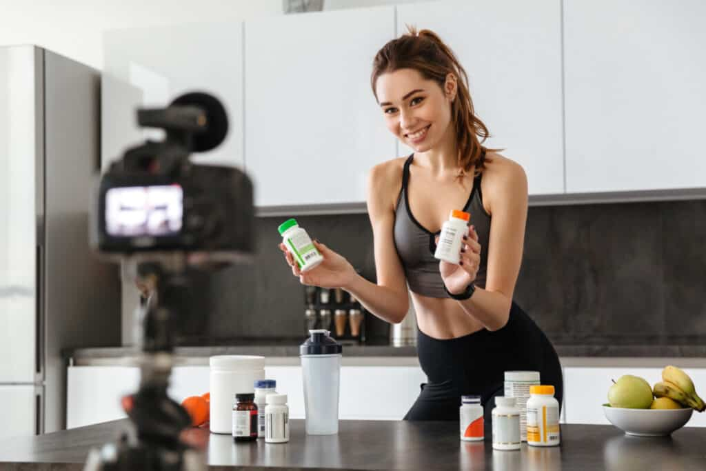 Smiling healthy young girl recording her video blog episode about checking to see if your supplements have expired.