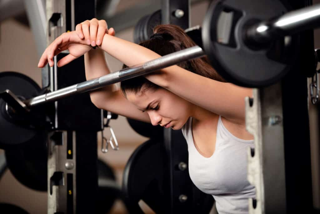 Very beautiful teenage girl resting and getting motivated between sets of barbell squats in gym. She keeps her eyes closed.