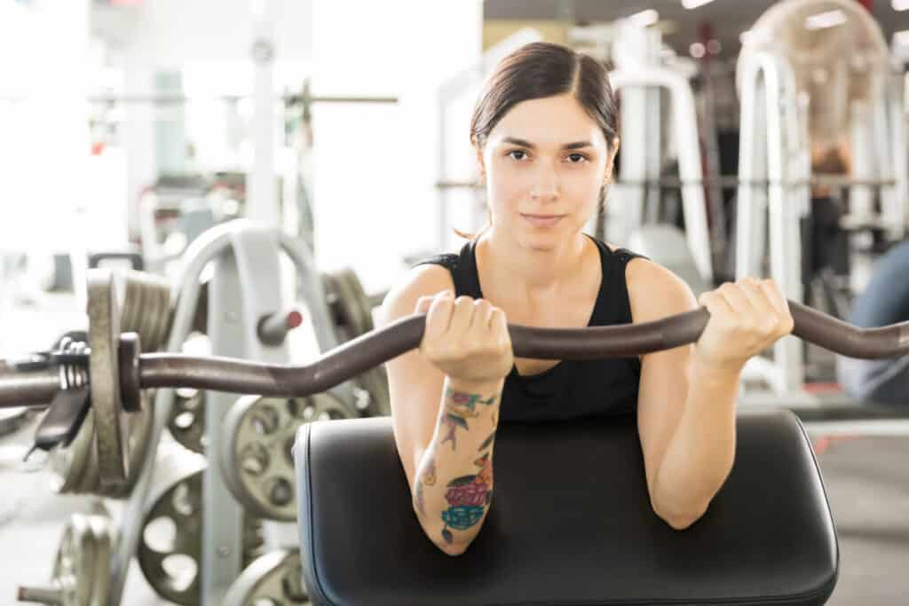 Portrait of confident female athlete lifting barbell curl on exercise machine in gym as part of her fitness routine while using trimtone