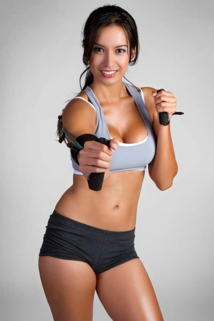 Beautiful smiling fitness woman exercising while using legal steroids for sale