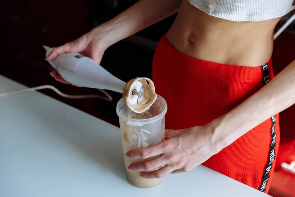 Woman with tight stomach making a protein shake meant for bulking