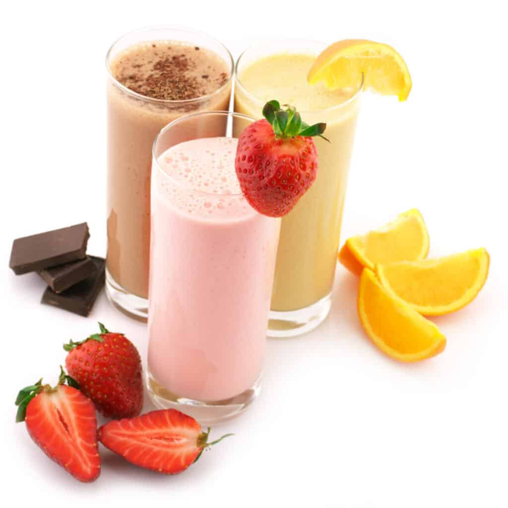 Three assorted protein shakes to gain weight cocktails with fruits isolated on white background.
