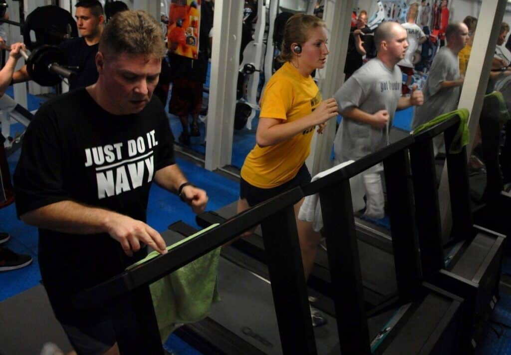 Men and women in a gym training on ellipticals